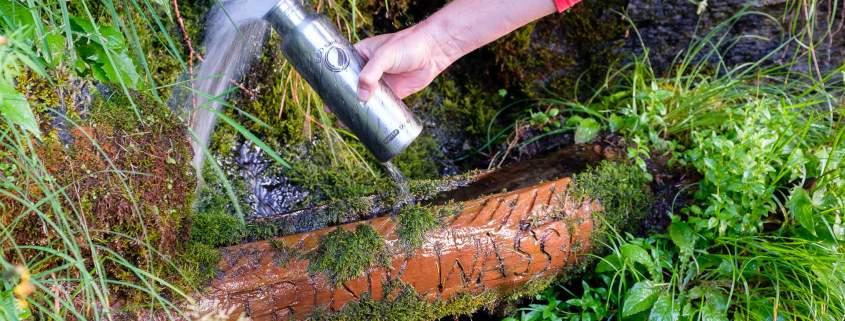 Eine ECOtanke Trinkflasche wird am Brunnen aufgefüllt